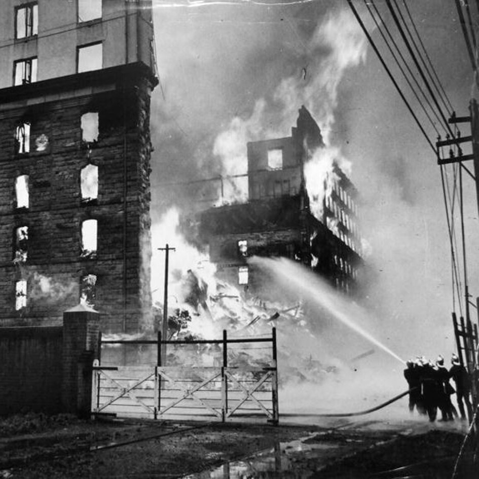 View showing firefighters using a hose to fight the blaze. The building was erected in 1881 and in 1922 an additional 3 floors were added. The fire started in the morning of the 25th September 1935. The whole of the Metropolitan Brigades were ordered out and there were 20 engines and about 230 men fighting the blaze.