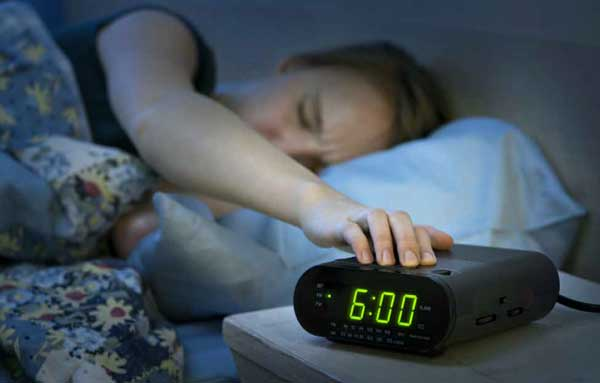 woman in her mattress turning her alarm clock off in the middle of the night