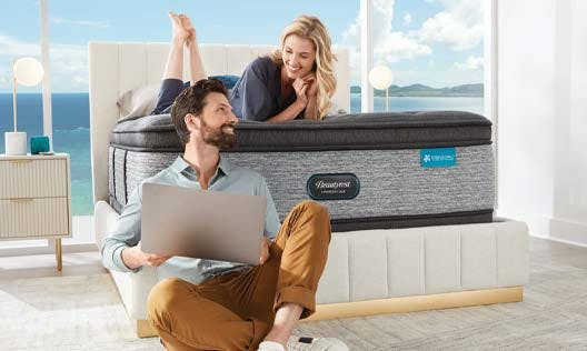 Wife and husband talking next to their new mattress