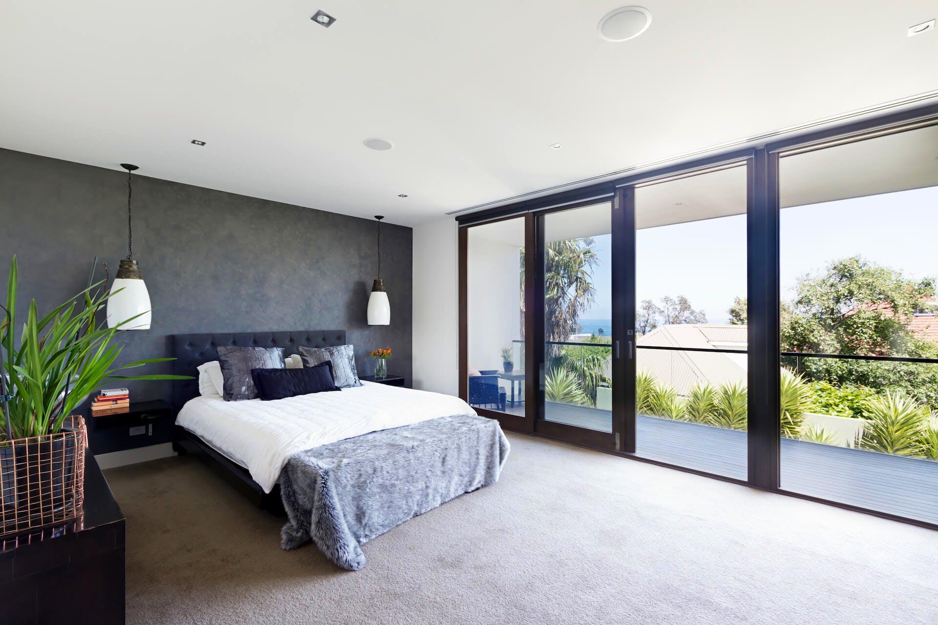 Sliding glass door with black frame in bedroom.
