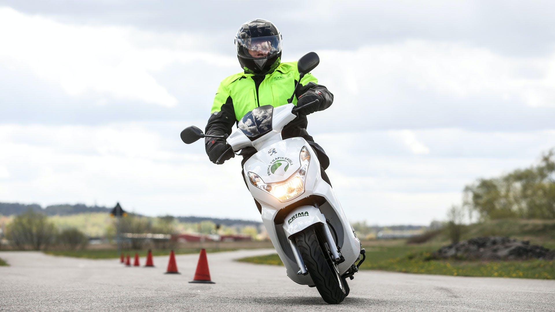 Moped som kör mellan konor