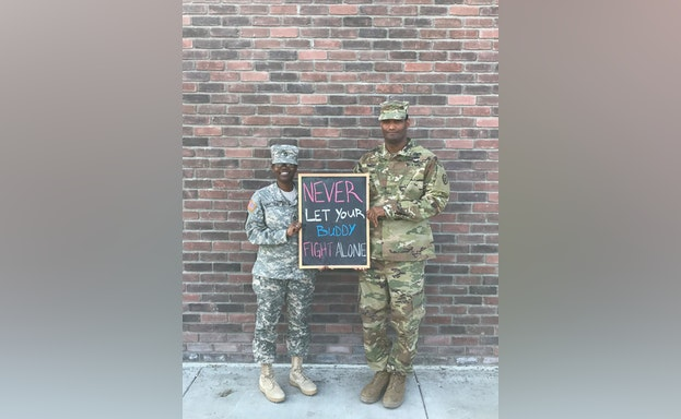 Man and woman in fatigues holding chalkboard