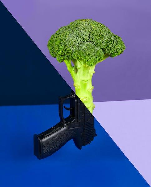 brócoli y pistola que simbolizan inversiones verdes y otras en industrias de armas
