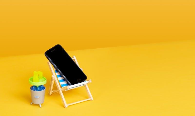 Ein Handy im Sonnenstuhl symbolisiert passiv investieren