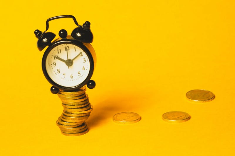 Ein Wecker und Geld, die symbolisieren, dass man schnell Geld verdienen kann