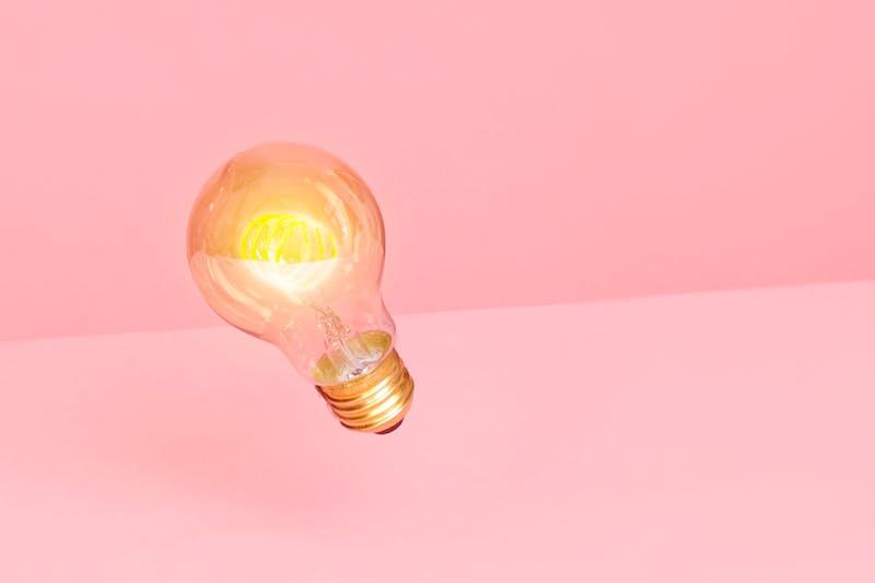 Eine Glühlampe, die für Finanztipps für junge Erwachsene steht