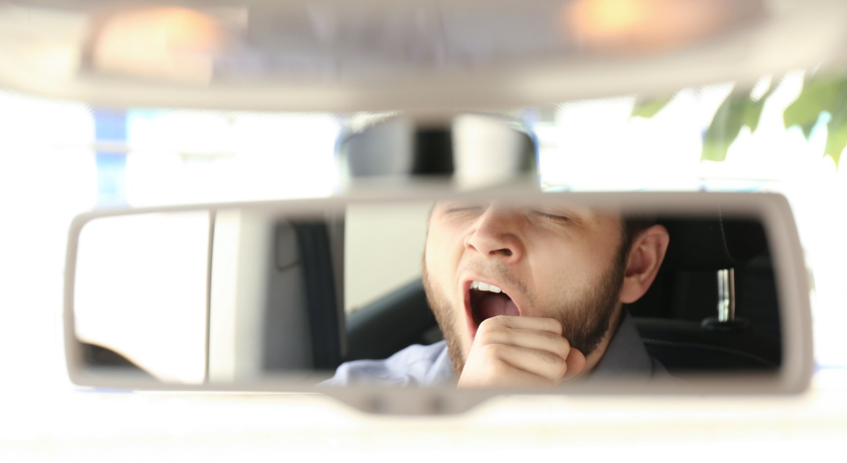 Photo of a rear view mirror reflecting a yawning driver