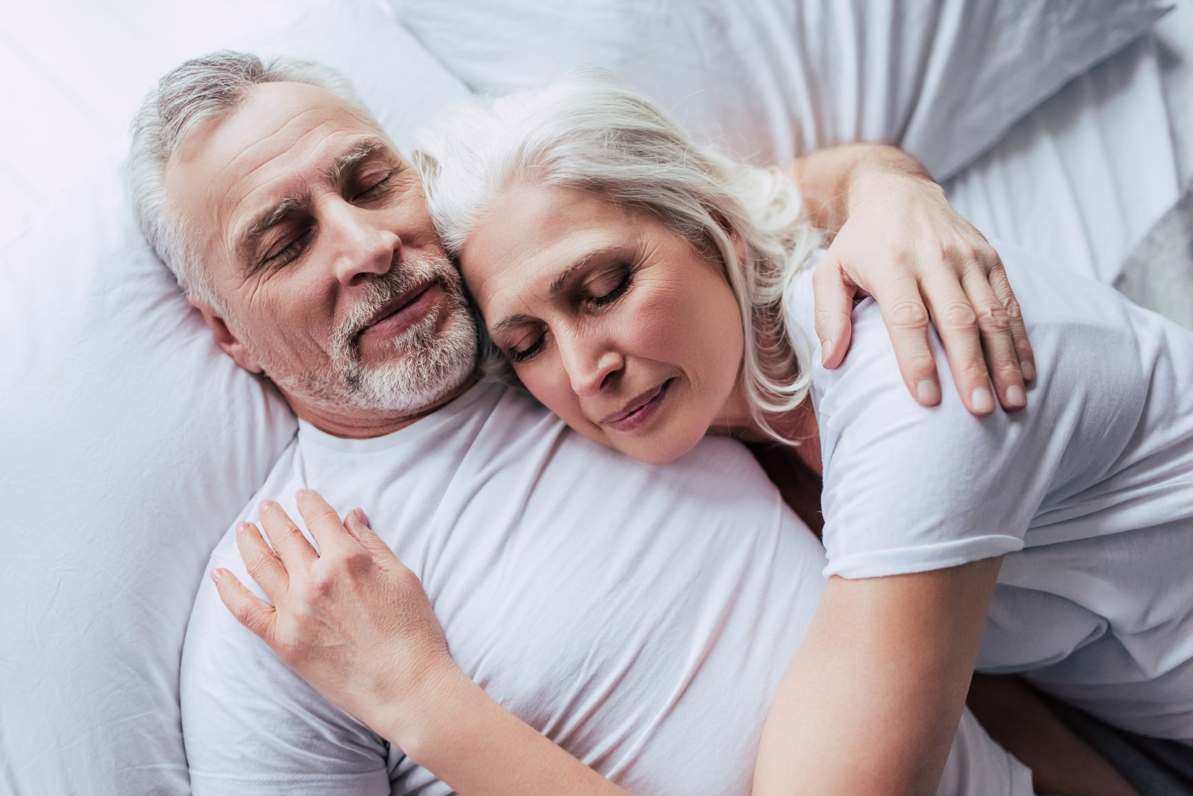 Older couple sleeping on their bed, the husband is gently holding his wife