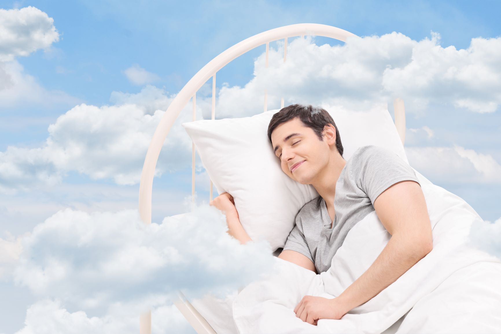 Man alseep on his bed floating in the clouds