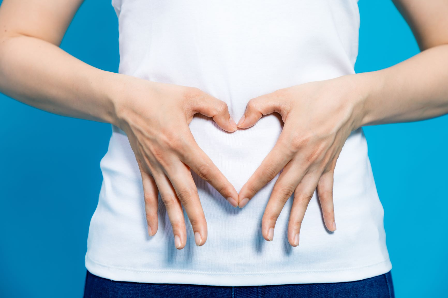 woman placing heart shaped fingers on stomach