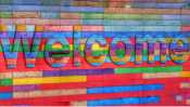 Color photo of a large, multicolored Welcome sign