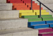 Color photo of a staircase with the steps painted the colors of the rainbow