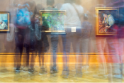 Long exposure color photo of people walking through a museum hall
