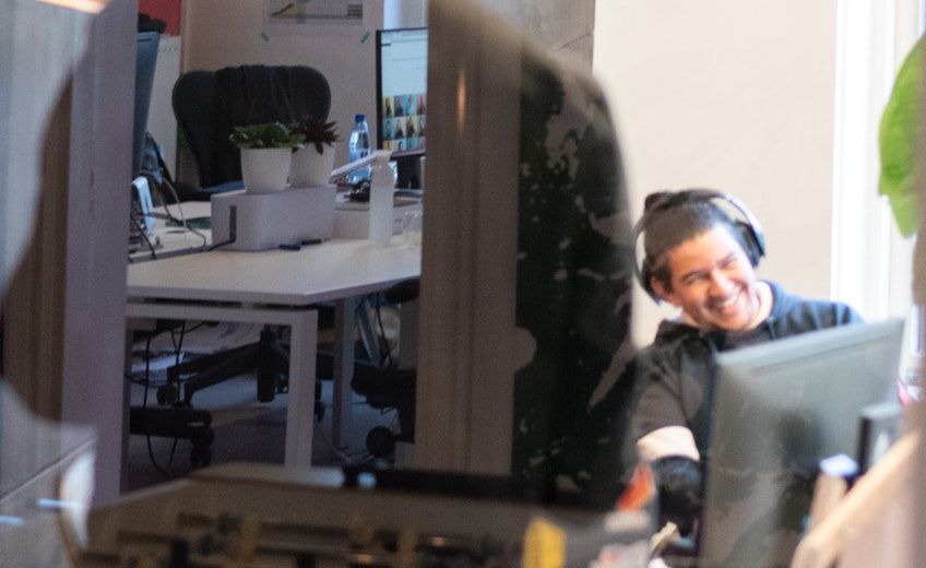 Een lachende developer gefotografeerd door het raam