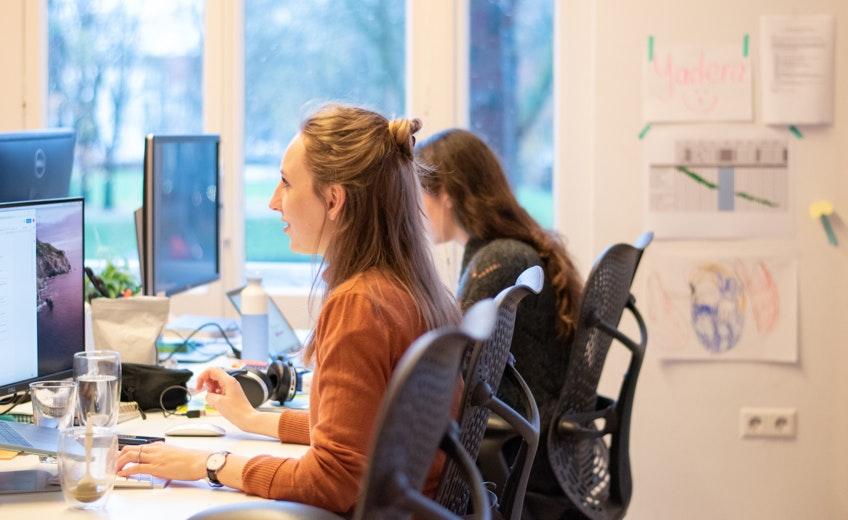 Mensen werken achter een computer met schetsen op de achtergrond