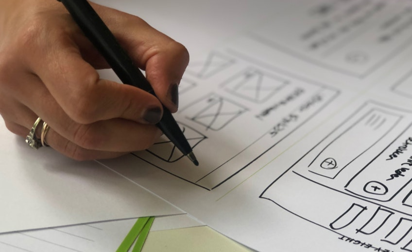 Een hand schetst een sitestructuur met een stift