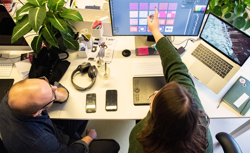 Twee collega's wijzen elkaar ontwerpen aan op een scherm