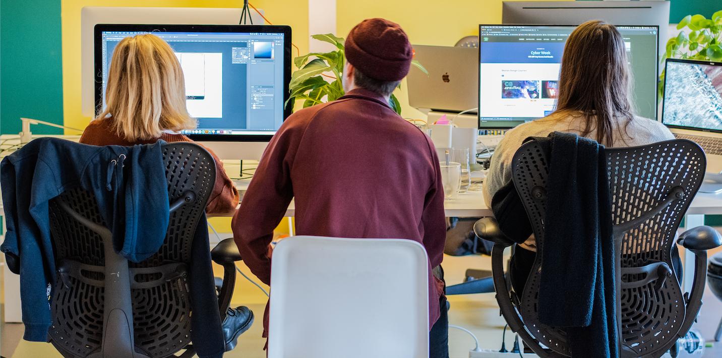 Drie collega's bekijken ontwerpen op twee schermen