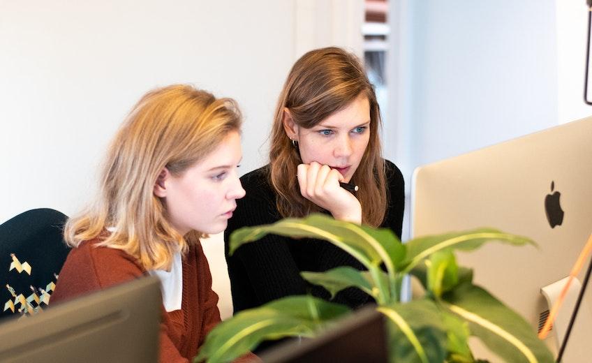 Twee collega's kijken naar een scherm