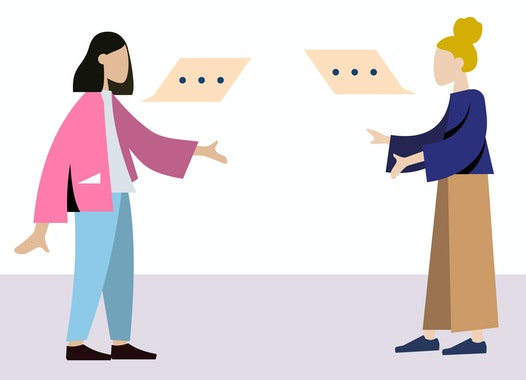 Twee personen staan tegenover elkaar en zijn in gesprek.