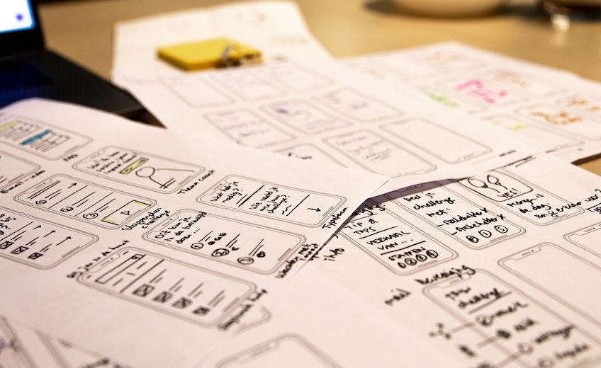 Stapel van papieren op tafel met schetsen in mobiele schermen.