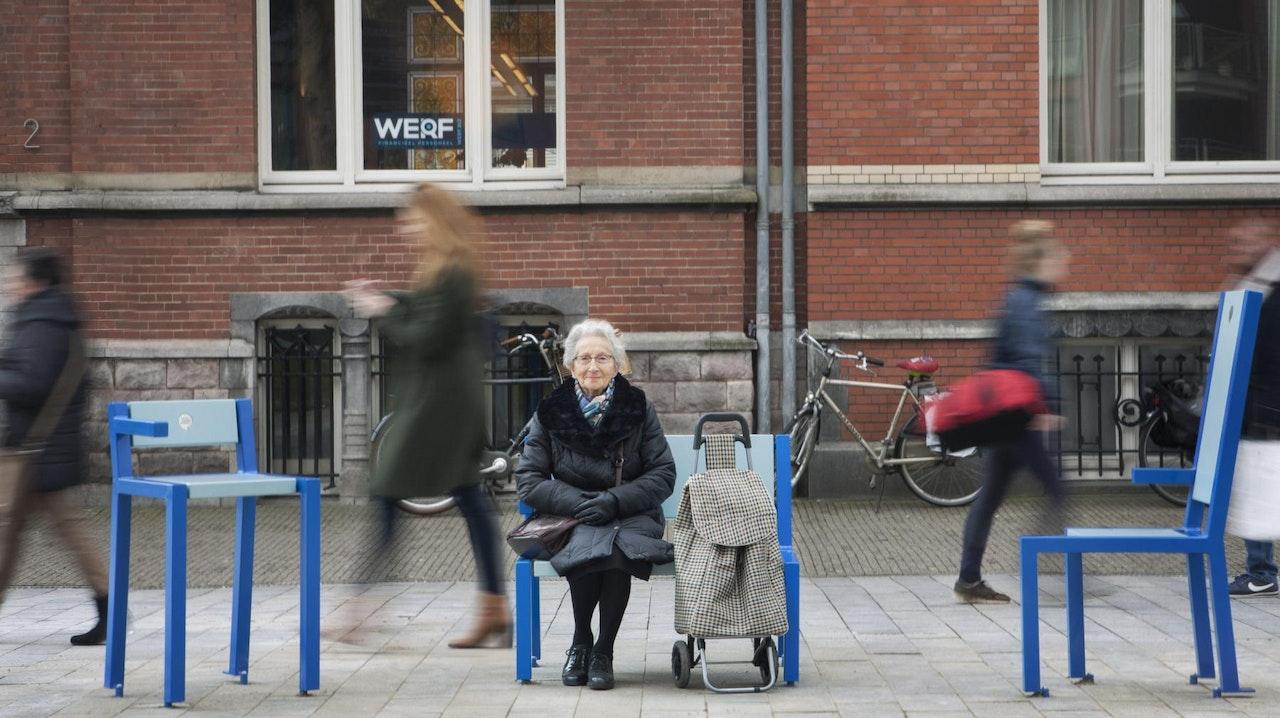 Een oudere mevrouw zit op een stoeltje, tussen twee lege stoeltjes in, er lopen mensen voorbij die wazig zijn alsof ze heel snel lopen