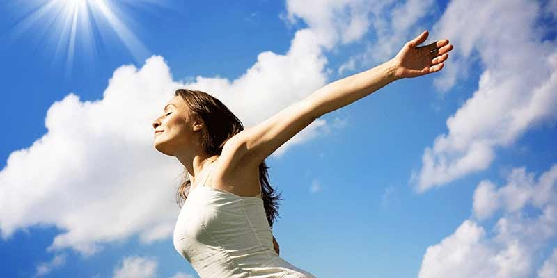woman in white dress with arms outstretched on sunny day