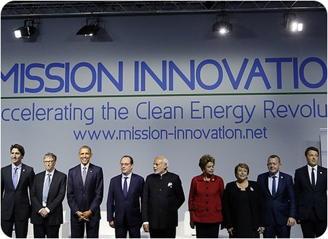 world leaders standing on stage in front of mission innovation banner