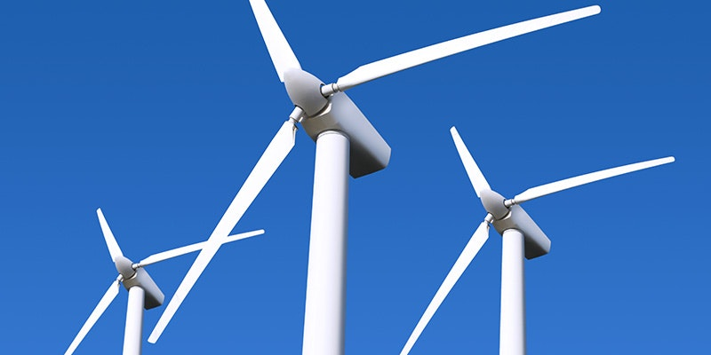 top section of 3 wind turbines against blue sky