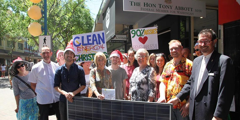 christians holding solar panel and positive solar signs in front of tony abbott's office
