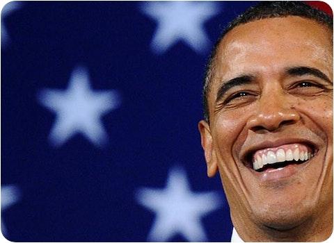 Barrack Obama smiling in front of American flag
