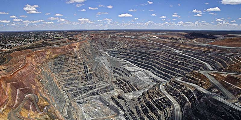 open cut coal mine with cloudy sky on horizon