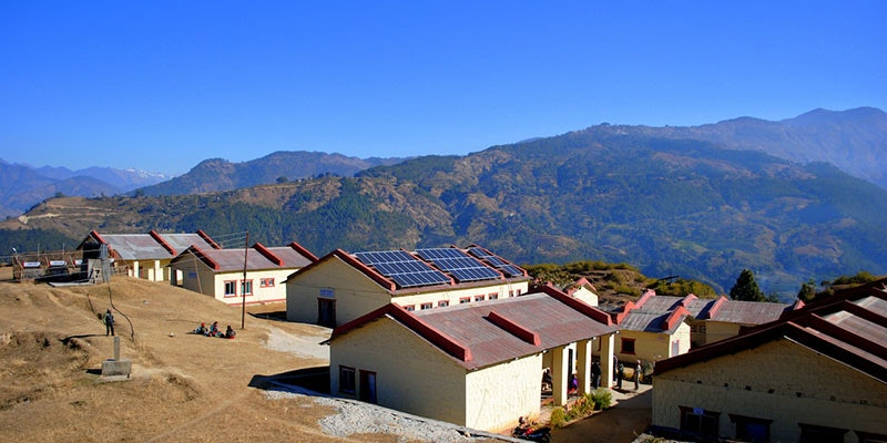 nepalese school with solar system installed and mountains and blue sky in background