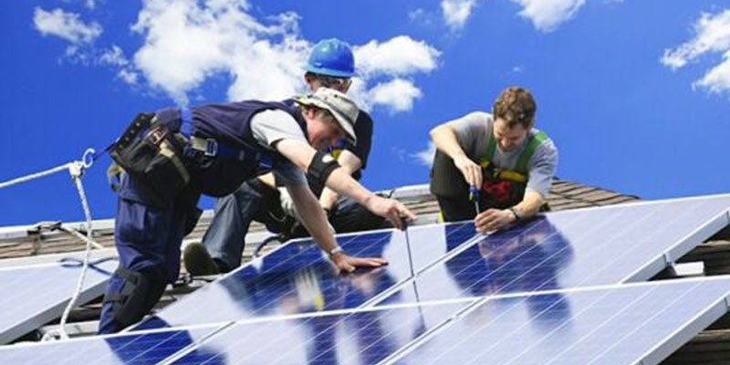 three solar installers installing solar panels on a tiled roof