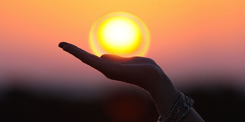 hand appearing to holding sun during beautiful sunset