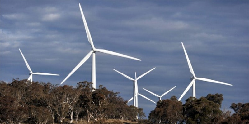 6 wind turbines mounted in woods with grey sky background