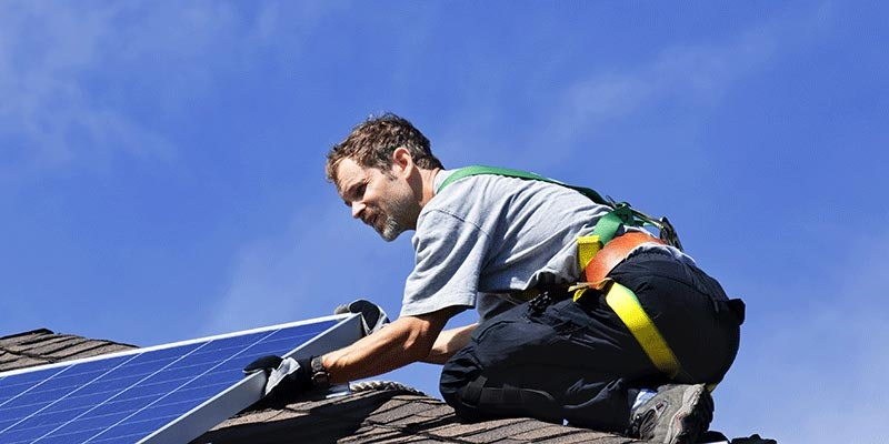 solar installer in harness mounting solar panel on tiled roof