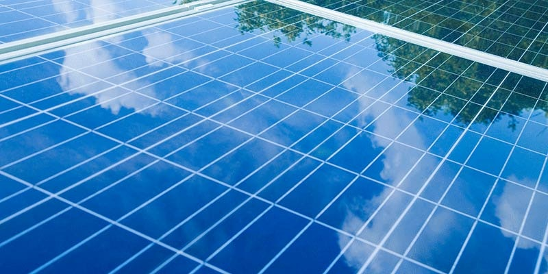 close up of 3 solar panels showing reflection of cloudy blue sky