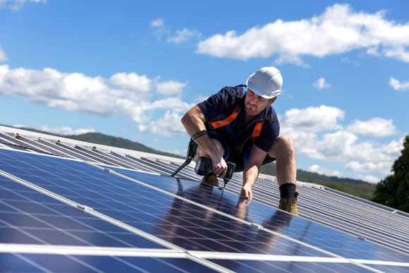 solar installer on roof checking solar panel tilt angle
