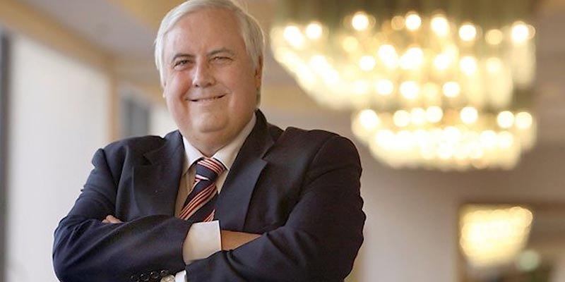 clive palmer in a suit with arms crossed looking happy