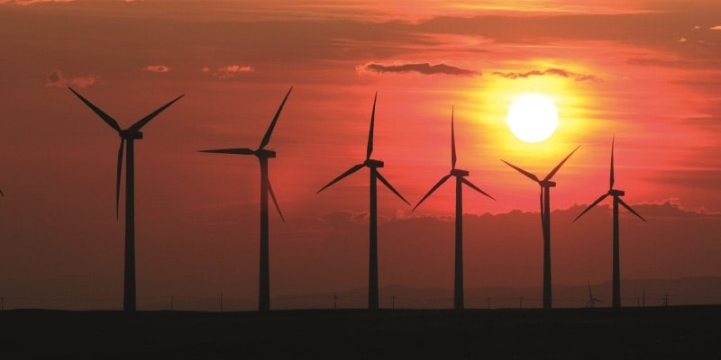 silhouette of 6 wind turbines at sunset