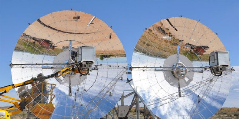 two 12m diameter mirrored ripasso solar energy dishes with blue sky background