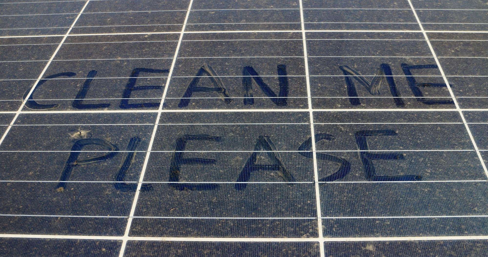 clean me please written on dirty solar panels