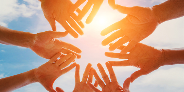 volunteering climate change photo looking at underside of hands joined in front of sun