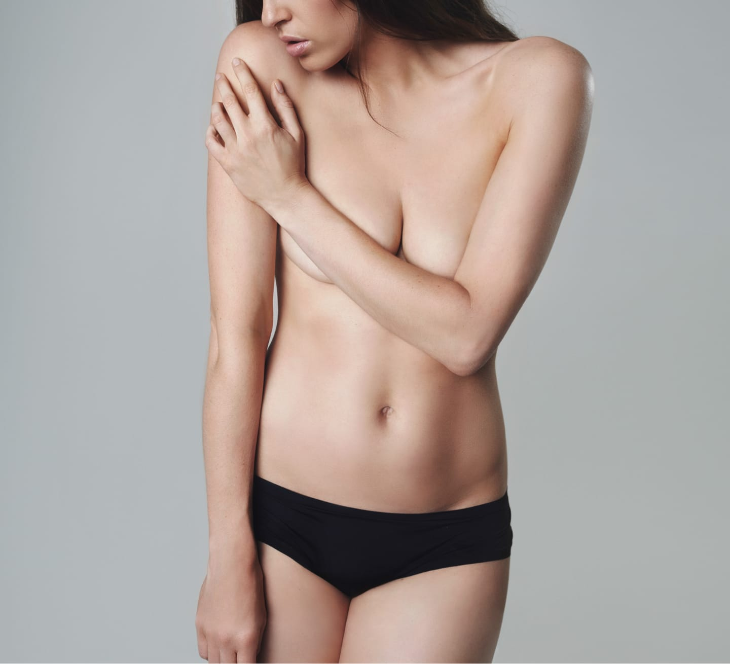 photo of woman in underwear covering breasts