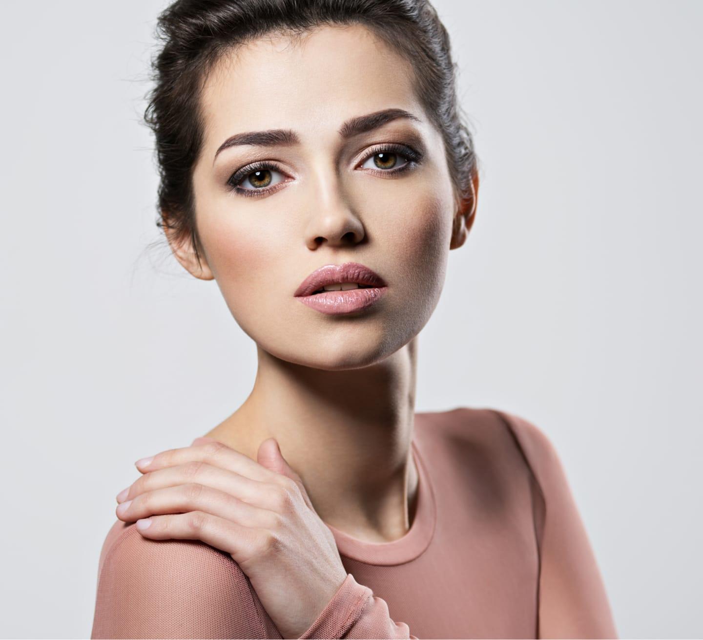 model holding shoulder and looking at camera
