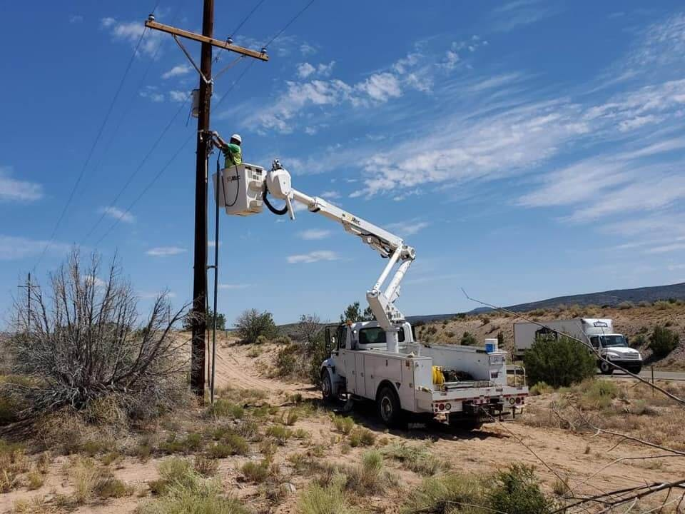 Allied Electric Inc working on Powerlines with bright blue sky