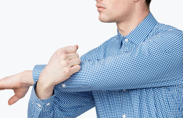 Men's Blue Gingham Aero Dress Shirt on Model Facing Forward with Arm Stretched Across Chest