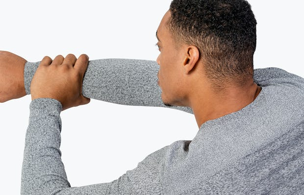 Men's Grey Static Sweater close shot of model facing away from camera doing an arm stretch