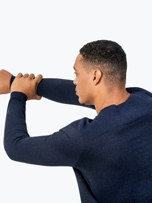 Men's Navy Static Sweater close shot of model facing away from camera doing an arm stretch